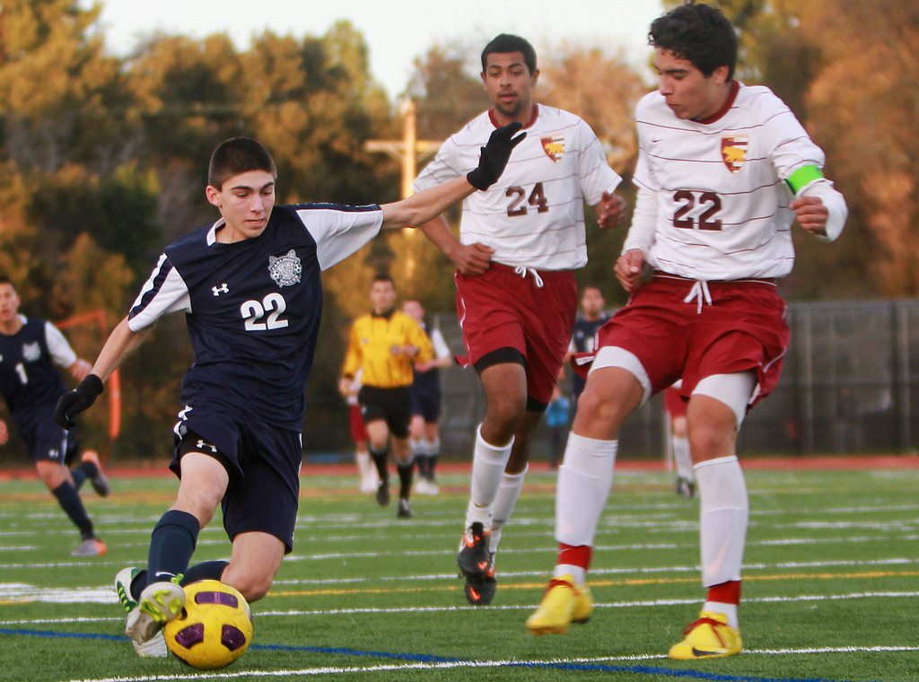 . Carlmont\'s Jordan Kiss kicks the ball toward the goal against Menlo-Atherton\'s Kevin Guierrez(cq), right, during a game in the second half during a game at Menlo-Atherton High School in Atherton on Monday, Jan. 28, 2013.  (Kirstina Sangsahachart/ Daily News)
