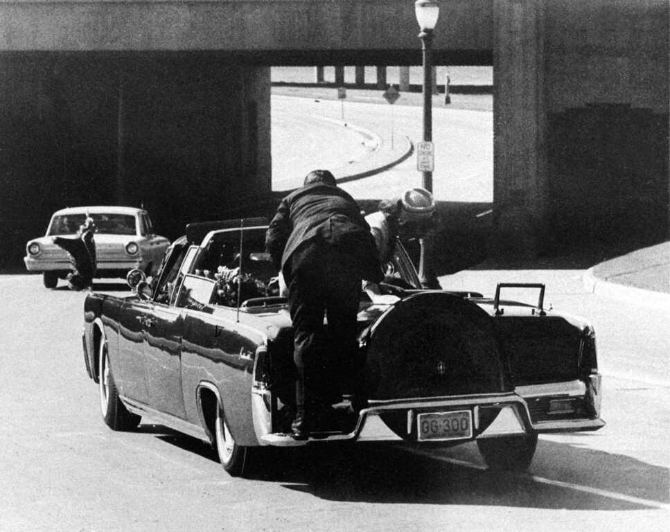 . President John F. Kennedy slumps down in the back seat of the Presidential limousine as it speeds along Elm Street toward the Stemmons Freeway overpass after being fatally shot in Dallas on Nov. 22, 1963.  Mrs. Jacqueline Kennedy leans over the president as Secret Service agent Clinton Hill rides on the back of the car.  (AP Photo/Ike Altgens)