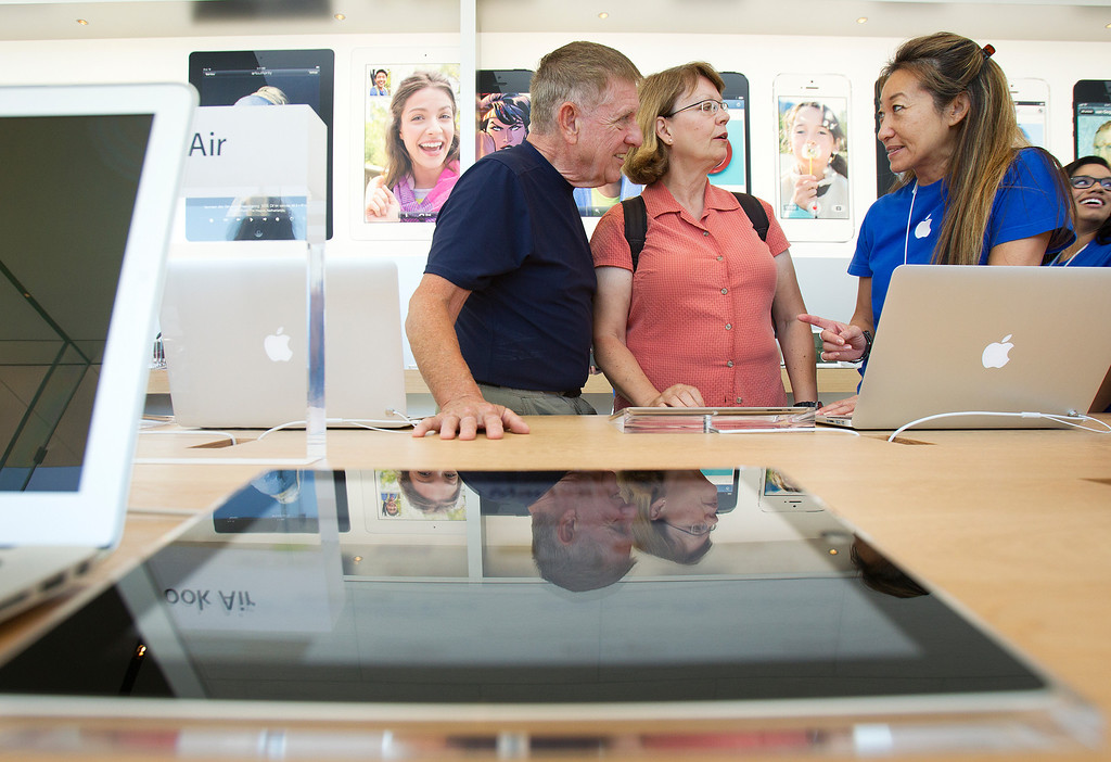 . Apple Business Specialist Mary Rye, right, speaks to Bernadette and Kevin Callahan at the redesigned Apple Store at the Stanford Shopping Center  in Palo Alto, Calif., on Saturday, Sept. 7, 2013.  (LiPo Ching/Bay Area News Group)