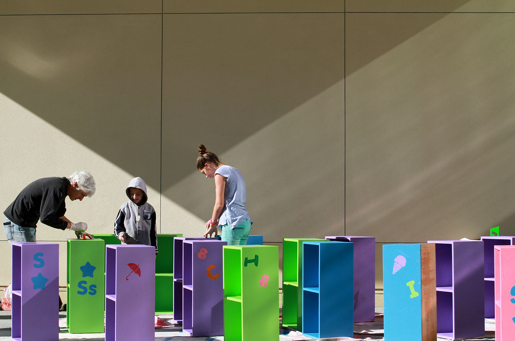. Volunteer Evan Smith, left, and his daughter Anya Zimmerman-Smith, 14, paint bookshelves for the nonprofit 10 Books A Home during the sixth annual Mitzvah Day for the Martin Luther King Jr. Day of Service at the Palo Alto Jewish Community Center in Palo Alto, Calif.,  on Monday, Jan. 21, 2013. Volunteers worked on 27 community projects on and off campus on Monday. (Kirstina Sangsahachart/Staff)