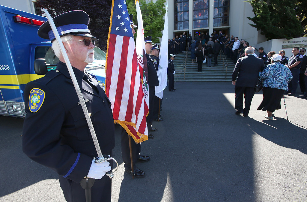 . Alameda County paramedic Ray Ericson, left, was part of the color guard during funeral services for Santa Clara paramedic Quinn Boyer, 34, of Dublin, at St. Theresa Catholic Church in Oakland, Calif., on Tuesday, April 16, 2013.  (Jane Tyska/Staff)