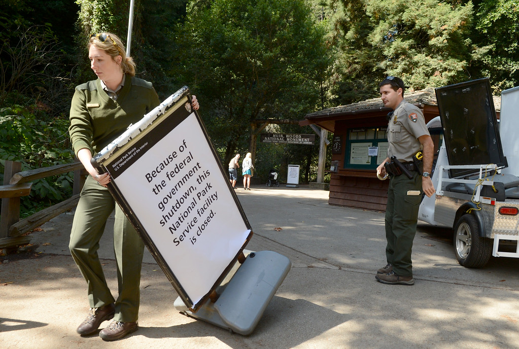 . Park rangers Sam Bell, left, and T. Henner place closed signs at the entrance to Muir Woods National Monument in Mill Valley, Calif. after the partial federal government shutdown on Tuesday, Oct. 1,  2013. (Alan Dep/Marin Independent Journal)