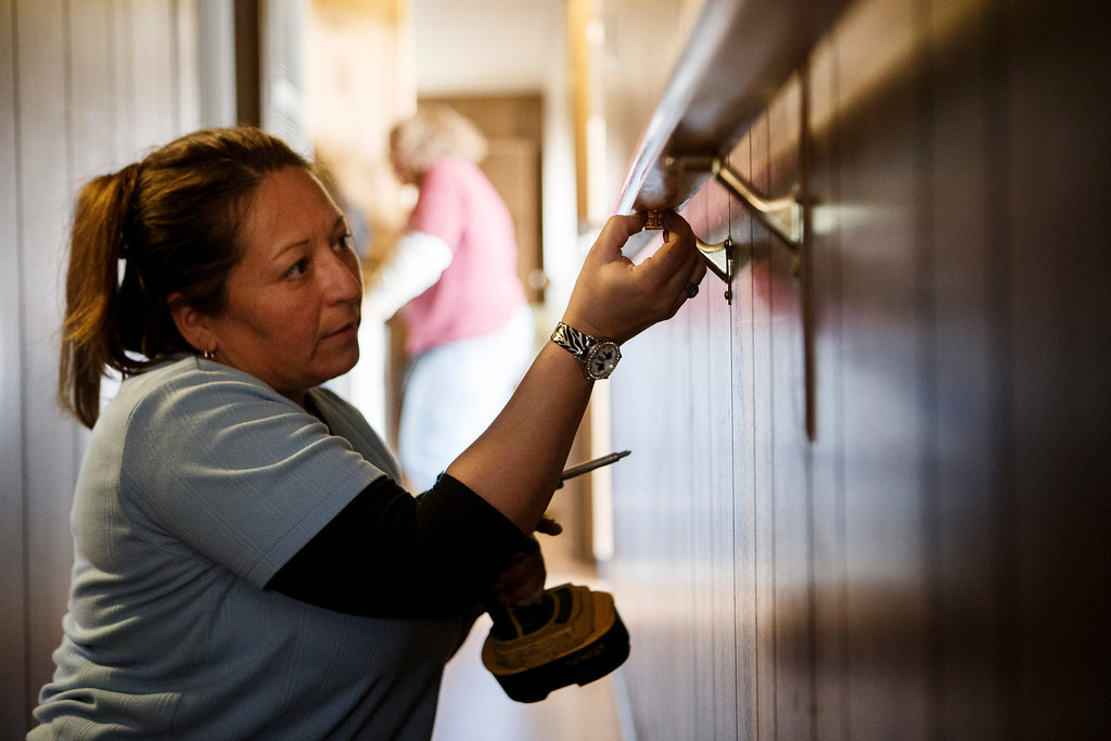 . Maria Januzys\' neighbor Lorraine Marquez helps repair efforts by  Rebuilding Together Silicon Valley at Januzys\' mobile home on Jan. 21, 2013 in Morgan HIll. The volunteers worked on various fixes including replacing the countertop and sink, replacing her front steps, installing shelving, and more. (Dai Sugano/Staff)