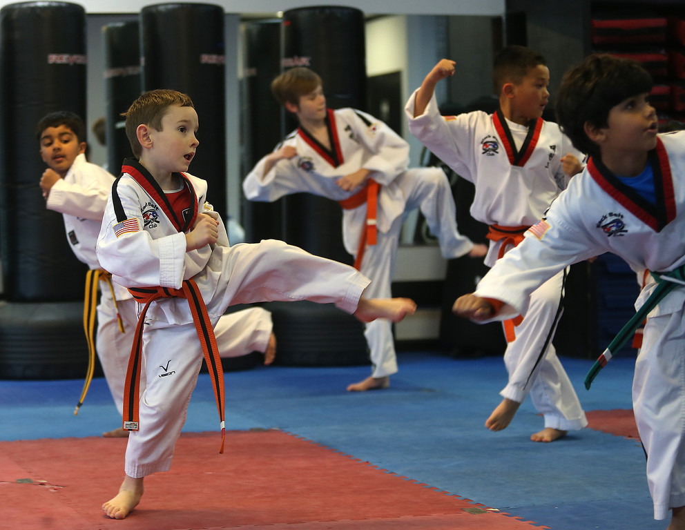 . Sammy Masek , 6,  left, takes part in a martial arts class on Monday, Feb. 11, 2013 in Pleasanton, Calif.  Masek is one of a growing number of children that have lost their diagnosis of autisim.  (Aric Crabb/Staff)