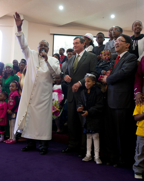 . Bishop J.W. Macklin of Glad Tidings Church of God, left, orchestrates a group picture of his school-age congregants with California State University Chancellor Timothy White and Cal State-East Bay President Leroy Morishita during a service at the church, Sunday, March 10, 2013 in Hayward, Calif. White and Morishita visited the church as part of the annual Super Sunday event to encourage African Americans to attend college. (D. Ross Cameron/Staff)