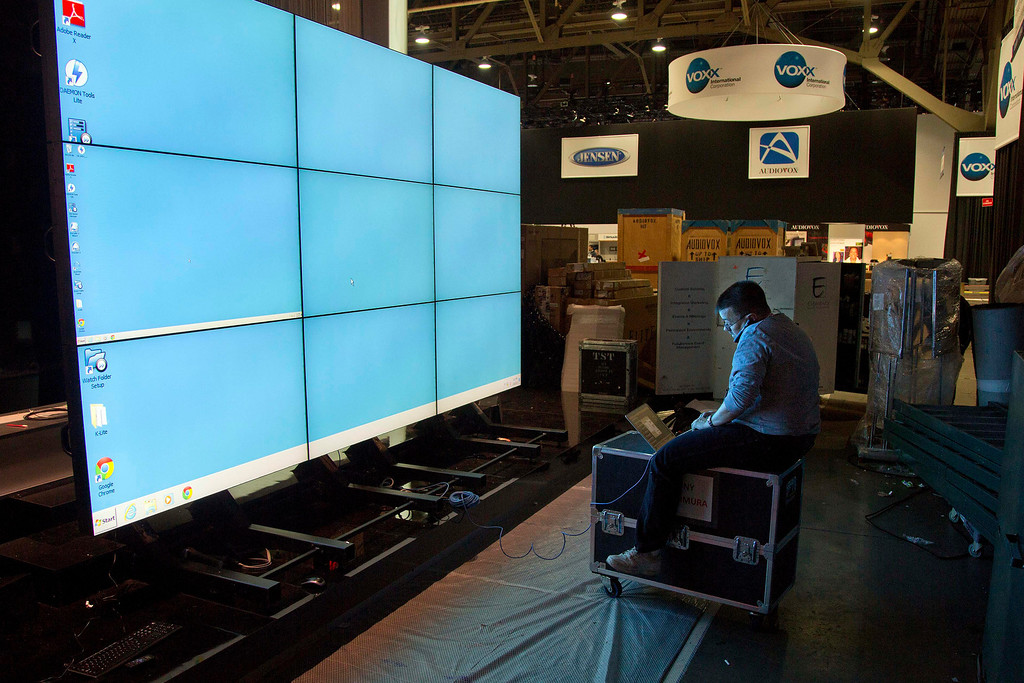 . Sharp Electronics employee Michael Nenortas programs a flat screen display at the company\'s booth for the International Consumer Electronics Show, Sunday, Jan. 6, 2013, in Las Vegas. The show, which drew more than 3,100 exhibitors in 2012 and is open only to industry affiliates, begins Tuesday and runs through Friday. (AP Photo/Julie Jacobson)