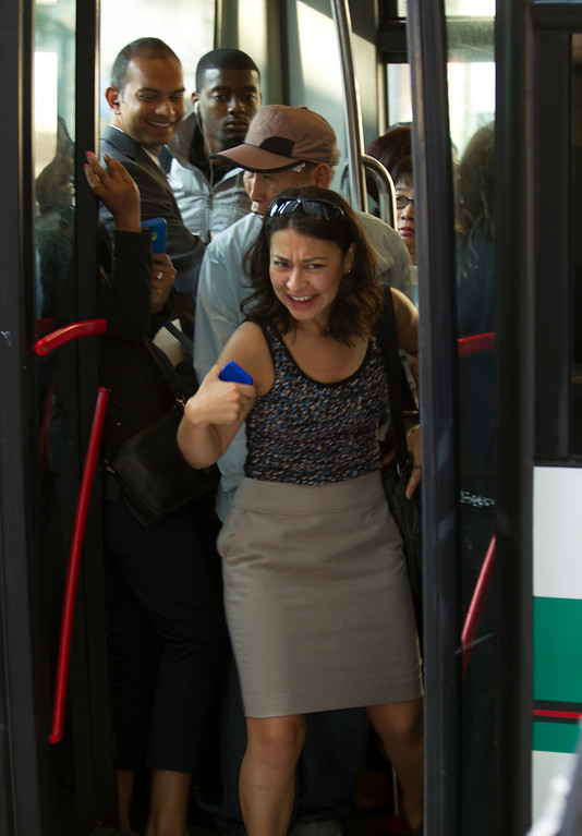 . A woman struggles to get out of a jam-packed AC Transit TransBay bus, as BART commuters scrambled to find alternative routes to San Francisco on the first day of a strike by workers of the mass transit system, Monday, July 1, 2013 in Oakland, Calif. (D. Ross Cameron/Bay Area News Group)