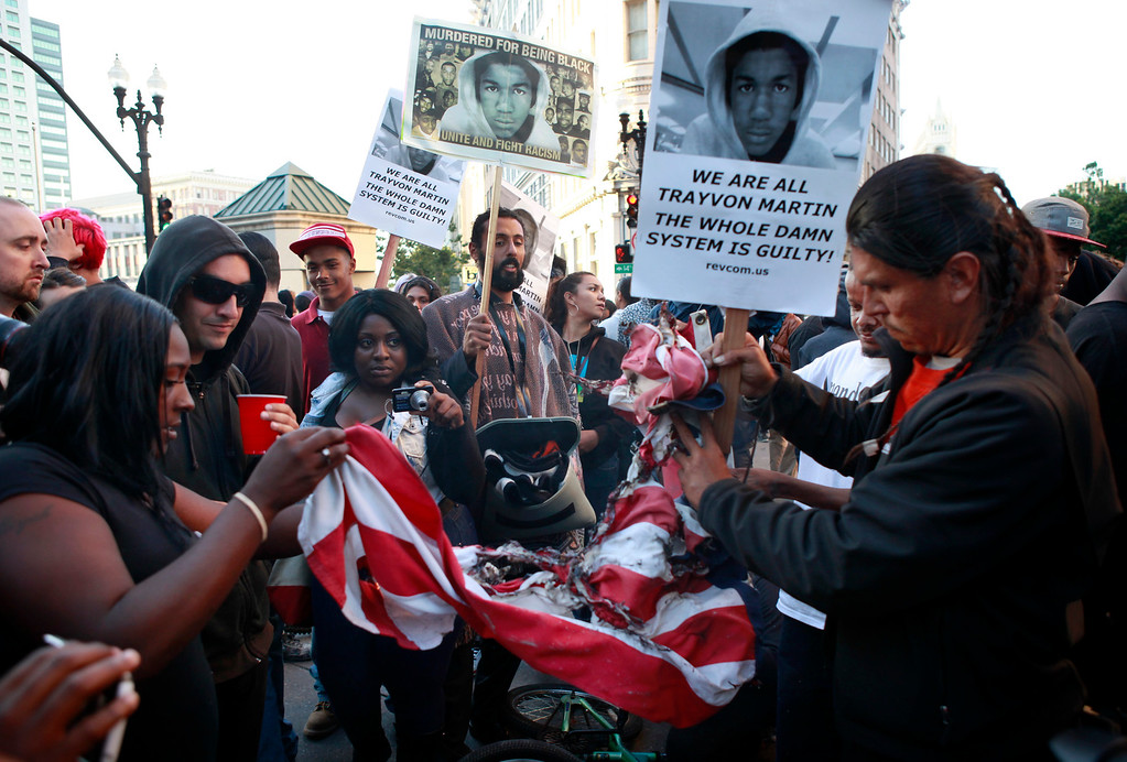 . After a peaceful two-hour march protesting the George Zimmerman acquittal, a few protesters attempt to burn an American flag at 14th and Broadway on Sunday evening, July 14, 2013 in Oakland, Calif. (Karl Mondon/Bay Area News Group)