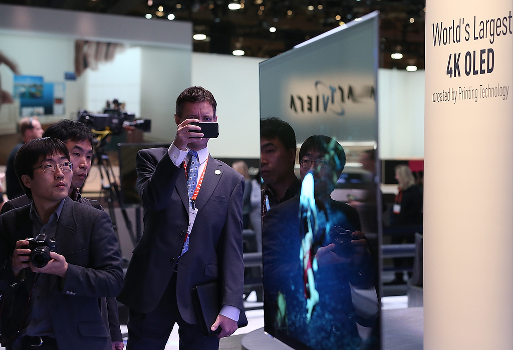 ". Attendees look at a display of the Panasonic 4K OLED 56"" television during the 2013 International CES at the Las Vegas Convention Center on January 8, 2013 in Las Vegas, Nevada. (Photo by Justin Sullivan/Getty Images)"