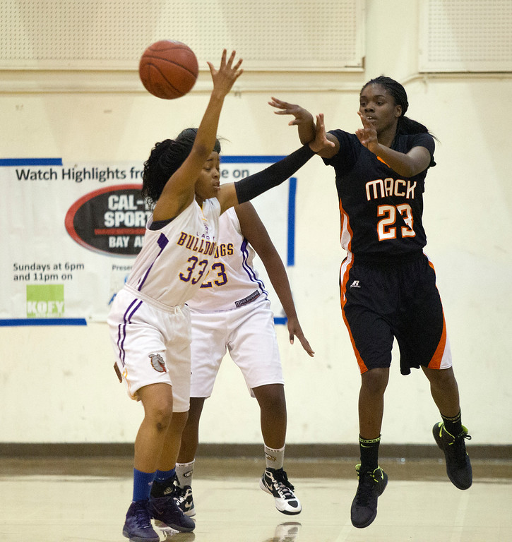 . McClymonds High School\'s Breannie Robinson (23) passes over Oakland Technical High School defender London Robinson (33) during the first quarter of their Oakland Athletic League girls\' basketball game, Wednesday, Feb. 20, 2013 in Oakland, Calif. McClymonds won, 62-50. (D. Ross Cameron/Staff)