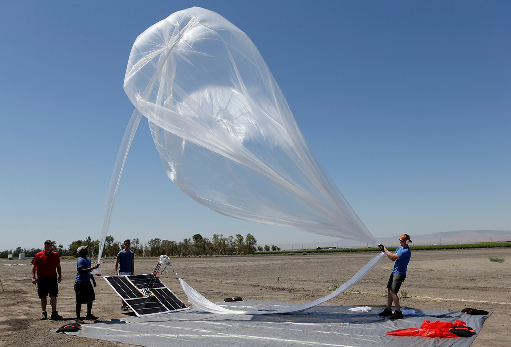 . The Project Loon team from Google launch a high-altitude balloon carrying electronic testing equipment into the skies above Dos Palos, Calif. on Friday, July 26, 2013. Team members from left to right are Bill Rogers, Hiyab Alemgesed, Michael Margraf and T.J. Tierney. The test launch is part of the research being done by  the Google X division to create a high-altitude transponder network that will provide internet access to underserved areas of the world.  (Gary Reyes/Bay Area News Group)