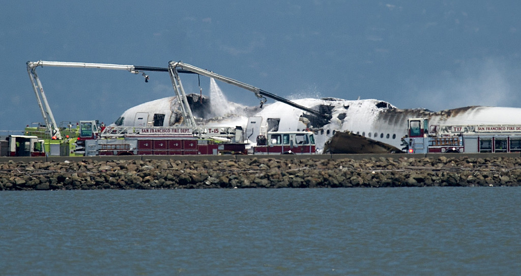 . A fire truck sprays water on Asiana Flight 214 after it crashed at San Francisco International Airport on Saturday, July 6, 2013, in San Francisco. (AP Photo/Noah Berger)