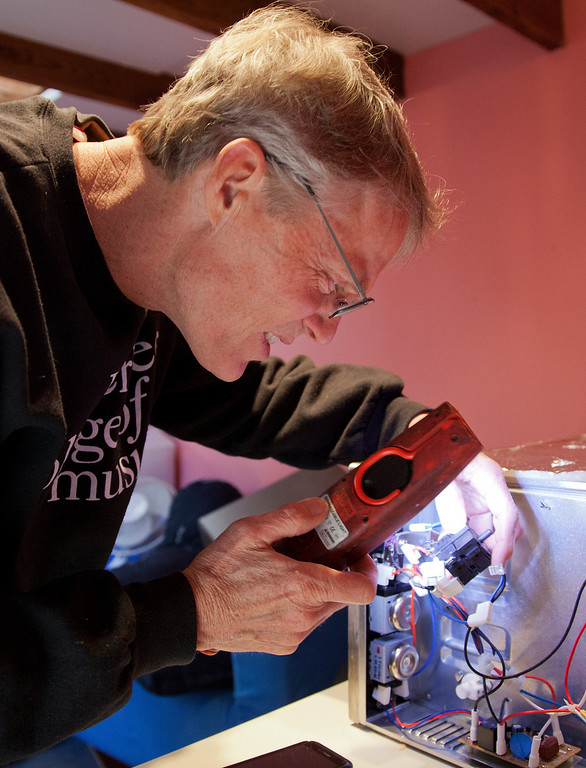 . John Eaton checks the contacts of the function dial of a neighbor\'s toaster oven after repairing it at his home in Palo Alto, Calif. on Friday, Feb. 15, 2013.   (LiPo Ching/Staff)