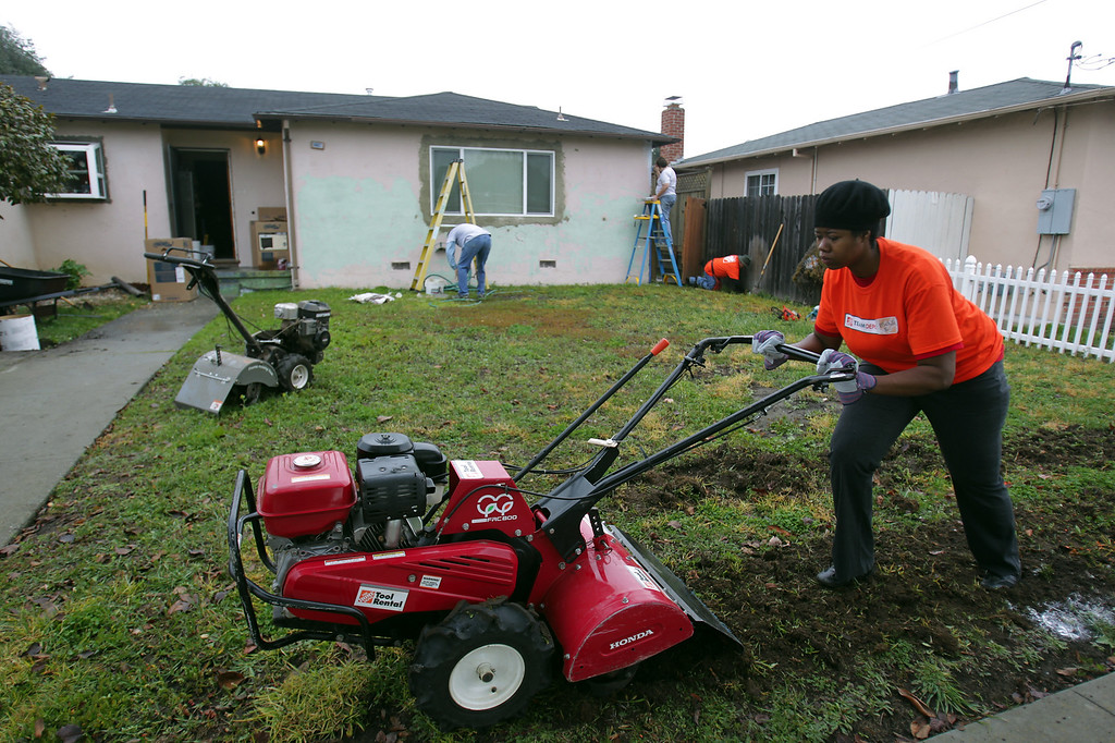 . Michelle Batte, of San Francisco, a volunteer with Home Depot uses a rototiller to prepare the front lawn for new sod at the home of Navy veteran Joseph Catalano in Hayward, Calif., on Thursday, Jan. 24, 2013. The Columbus, Ga. nonprofit House of Heroes is partnering with Home Depot to repair 36 houses owned by military and public safety veteran or their spouses  around the nation. (Anda Chu/Staff)