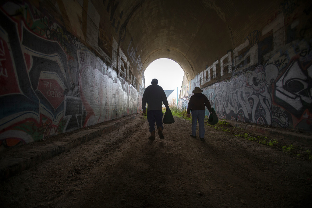 . Jim McKissock,left, with Earthcare Now and volunteer Gail Wilson walk through an old railroad tunnel after rescuing tadpoles in Brisbane.(John Green/Staff)