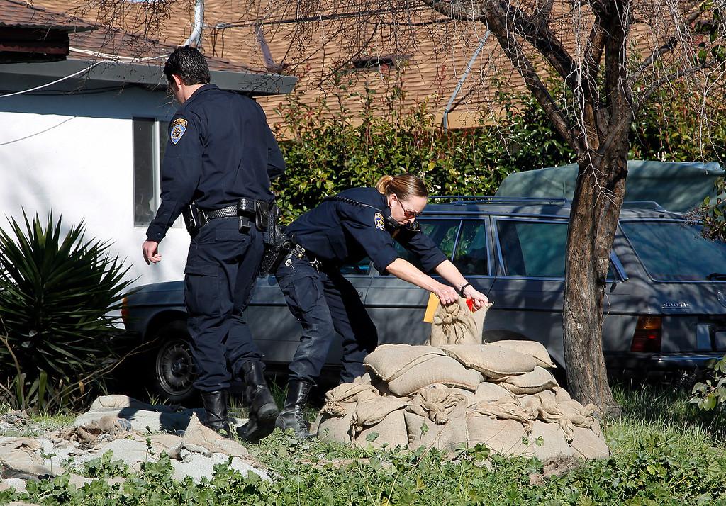 . California Highway Patrol officers prepare sandbags to detonate destructive devices found at Everett Basham\'s house on Humbolt Ave., in Santa Clara, Calif. on Wednesday, Feb. 13, 2013.   (LiPo Ching/Staff)