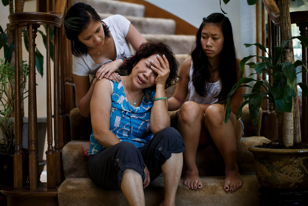 . Sitting near her four daughters recounting about the death of their brother, Vince Canh Xuan Nguyen, to this newspaper, the mother, Linda-Hoa Duong, is comforted by her daughter Dalena Nguyen, left, and her niece, Katie Phan, 14, at her home on July 16, 2013 in San Jose.  The San Jose family believes there may be foul play behind the death of Vince Canh Xuan Nguyen, who passed away in a tiny hotel room in Vietnam on July 1, 2013, after a night of drinking ended with him gravely ill, unable to control his body functions. (Dai Sugano/Bay Area News Group)