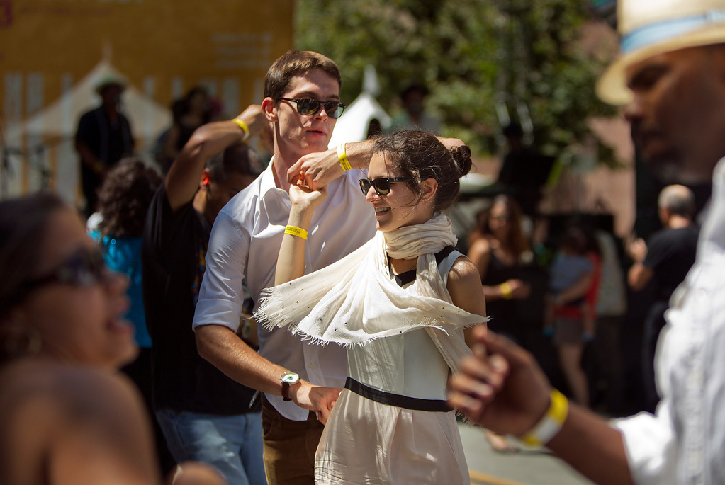 . From center left, Vincent Gonguet and Louise Corron dance near the Kaiser Permanente Salsa Stage at the San Jose Jazz Festival, in San Jose, Calif., on Saturday Aug. 10, 2013.  (LiPo Ching/Bay Area News Group)