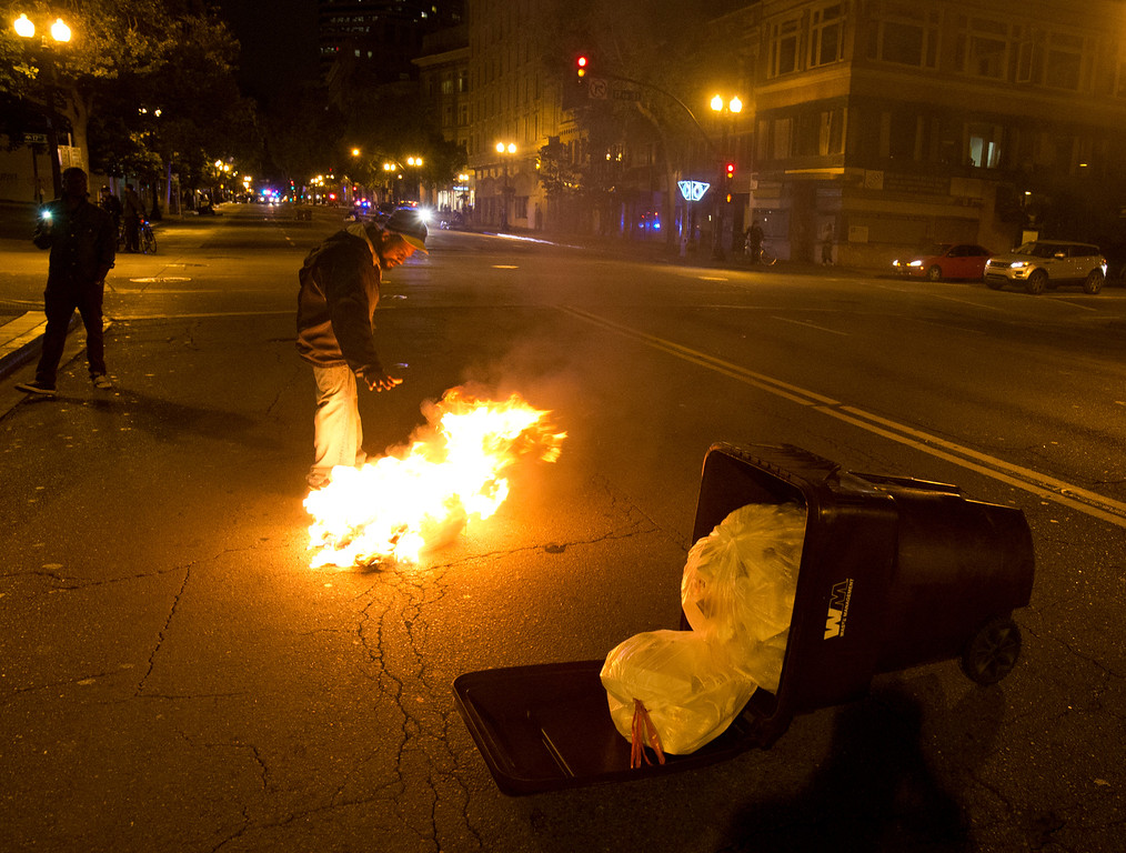 . An unidentified man warms his hands over a bag of burning trash on Broadway left by demonstrators during a protest of the verdict in the Trayvon Martin murder trial last Saturday in Sanford, Fla., Monday, July 15, 2013 in Oakland, Calif. (D. Ross Cameron/Bay Area News Group)