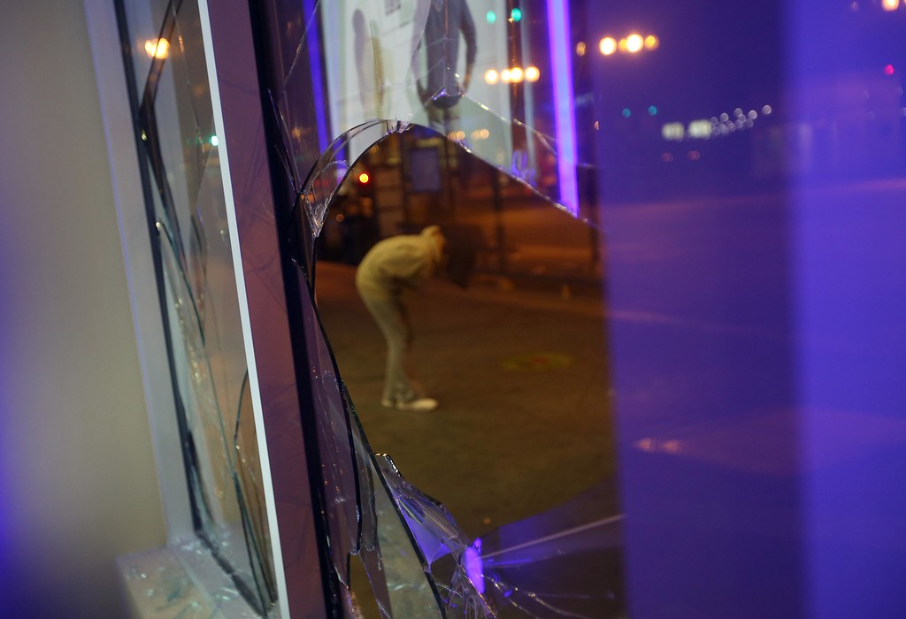 . A street person is seen through a smashed window at the Chase Bank on Broadway and 14th Street in downtown Oakland, Calif., early Sunday, July 14, 2013. Protesters also lit several small fires on Telegraph Avenue and sprayed graffiti after learning that George Zimmerman had been found not guilty in the shooting death of Trayvon Martin in Sanford, Fla. (Jane Tyska/Bay Area News Group)