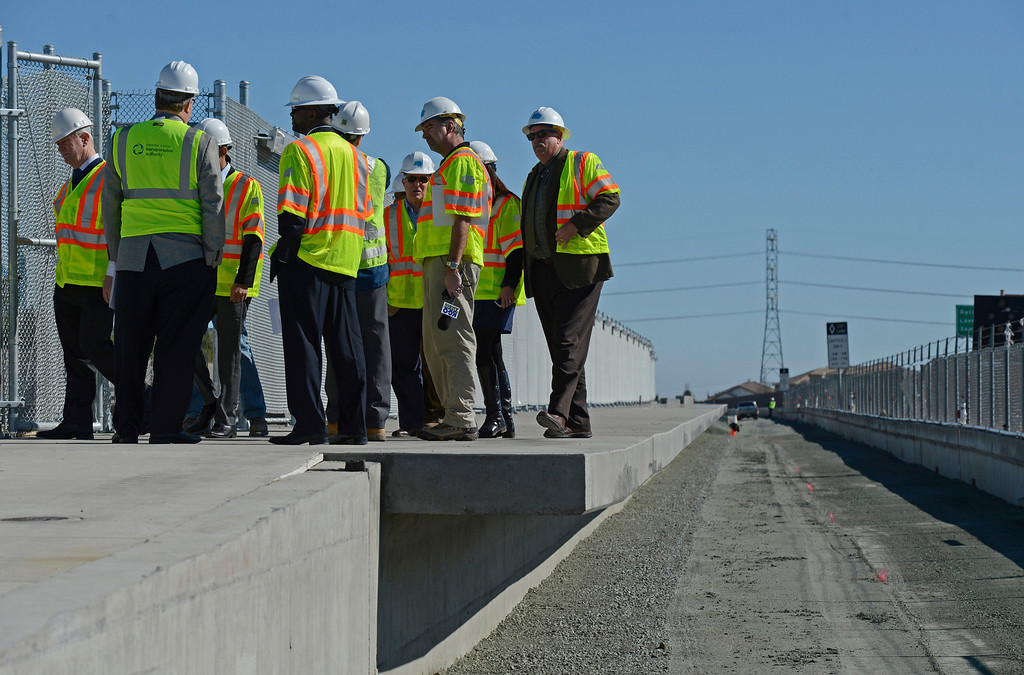 . City and state officials stop to examine the future eBART platform located east of the BART station on Bailey Road  on Highway 4 in Pittsburg, Calif., on Monday, Feb. 11, 2013. Members of the media with state and local city officials traveled on a bus tour of the Highway 4 expansion project in East County. The tour took visitors to construction sites on Railroad Ave and the new eBART station being built on Bailey Road. (Jose Carlos Fajardo/Staff)