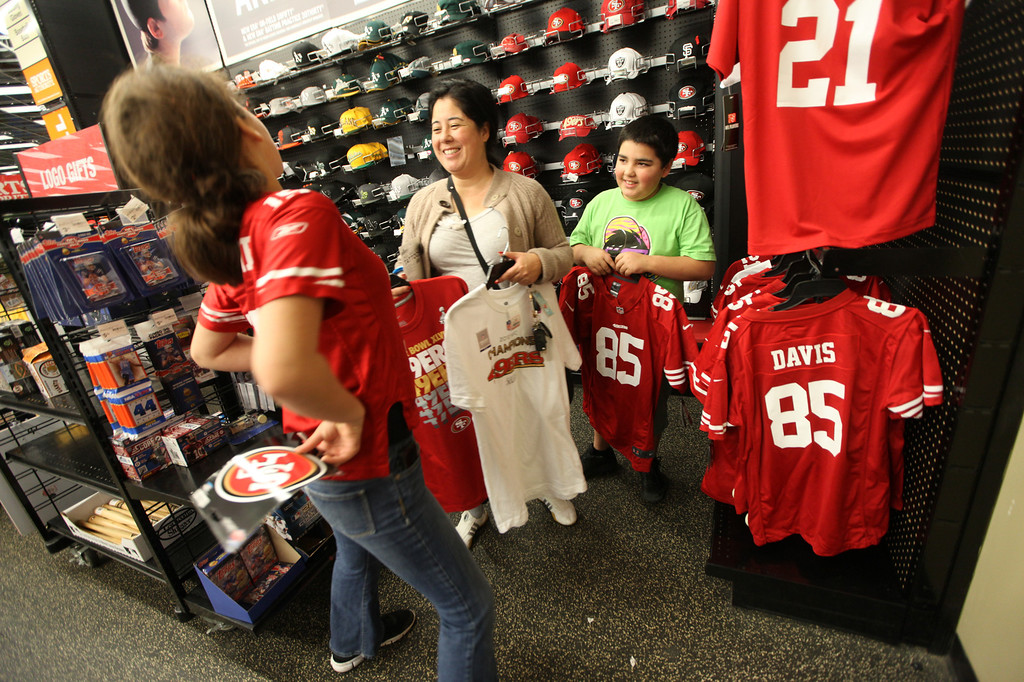 . Emma Meadows, 12, does a fashion pose for her mother, Yukiko Meadows, and brother, Miles Meadows, 11, as they shop for 49ers merchandise at Sports Authority in San Francisco, Calif., on Monday, Jan. 21, 2013. (Laura A. Oda/Staff)