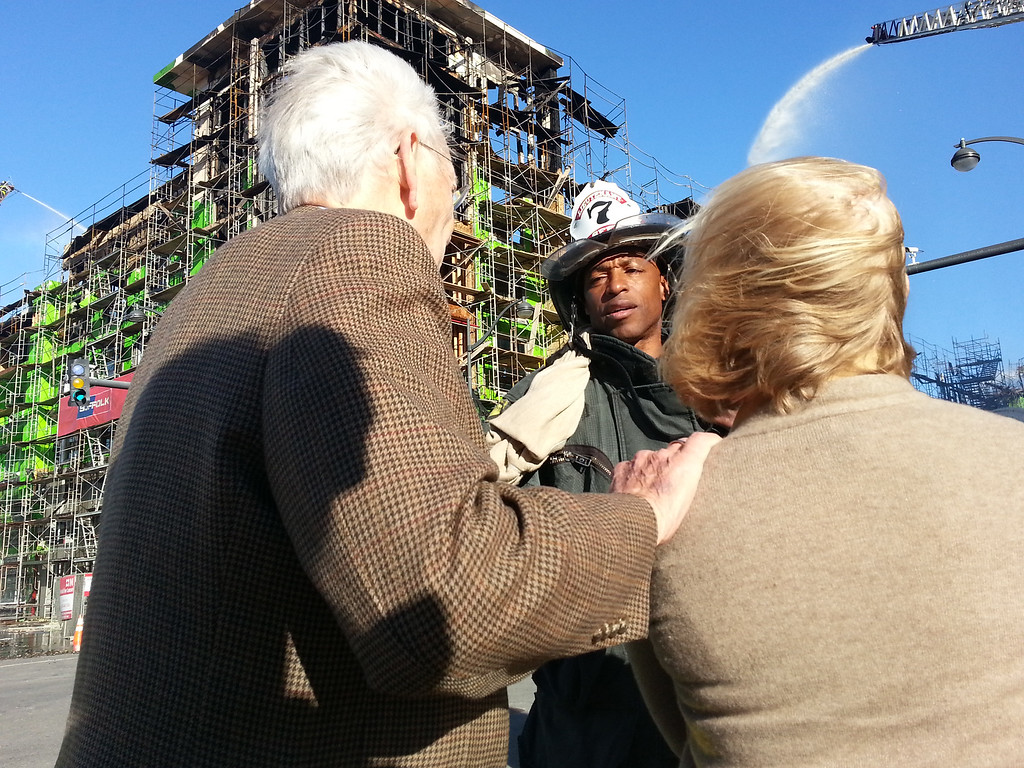 . A firefighter tells nearby residents Patricia and Dr. Davis Baldwin that they will need to be escorted into their apartment building as firefighters continue to pour water on hotspots the day after a fire destroyed an apartment building that was under construction in San Francisco on Wednesday, March 12, 2014.     (Courtesy of Chris Baldwin)