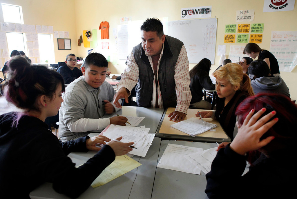 . Daniel Mencilla helps out during a class on College Readiness at ACE Charter High School in San Jose, Calif. on Wednesday, Dec. 05, 2012. Mencilla was the school\'s physical education teacher before that class was dropped. He was helping students (l-r) Lindeysi Magana, Oscar Melara, Consuelo Barajas and Jennifer Lopez make a list of possible college selections. The College Readiness class has also been dropped from the curriculum. (Karl Mondon/Staff)