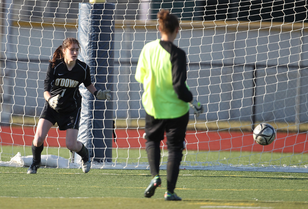 . Piedmont goalie Kesy Platt scores a penalty kick against Bishop O\'Dowd goalie Lorna McElrath (1) in the North Coast Section Division II Girls Soccer Championship at Dublin High School soccer field in Dublin, Calif., on Saturday, Feb. 23, 2013. Bishop O\'Dowd won 3-2 in a series of penalty kicks. (Ray Chavez/Staff)