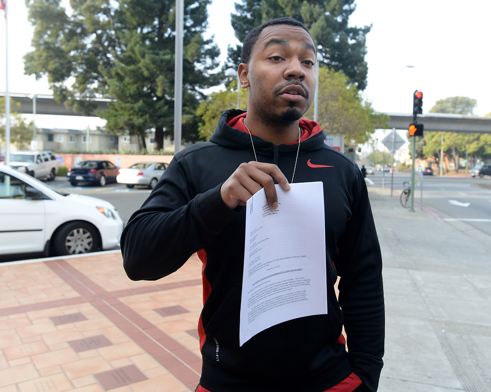 . Omari Sealey, 27, shows members of the media a letter to cease and desist from attorney Christopher Dolan in front of Oakland\'s Children\'s Hospital in Oakland, Calif., on Tuesday, Dec. 17, 2013. The hope is that the letter will prevent the hospital from doing anything further to Sealey\'s niece, 13-year-old Jahi McMath, 13, who was declared brain dead following complications from a three-part surgery to remove her tonsils and clear tissue from her nose and throat to treat her sleep apnea and other health issues. She remains in the hospital on a ventilator. (Dan Honda/Bay Area News Group)