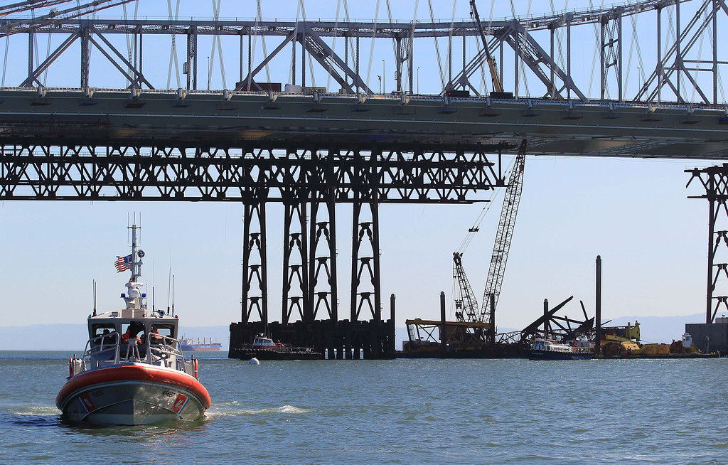 . A Coast Guard boat guards the safety zone after a barge crane, right, collapsed while removing iron falsework from the new Oakland-San Francisco Bay Bridge project in San Francisco, Calif. on Thursday, Feb. 21, 2013. No one was injured in the incident. (Jane Tyska/Staff)