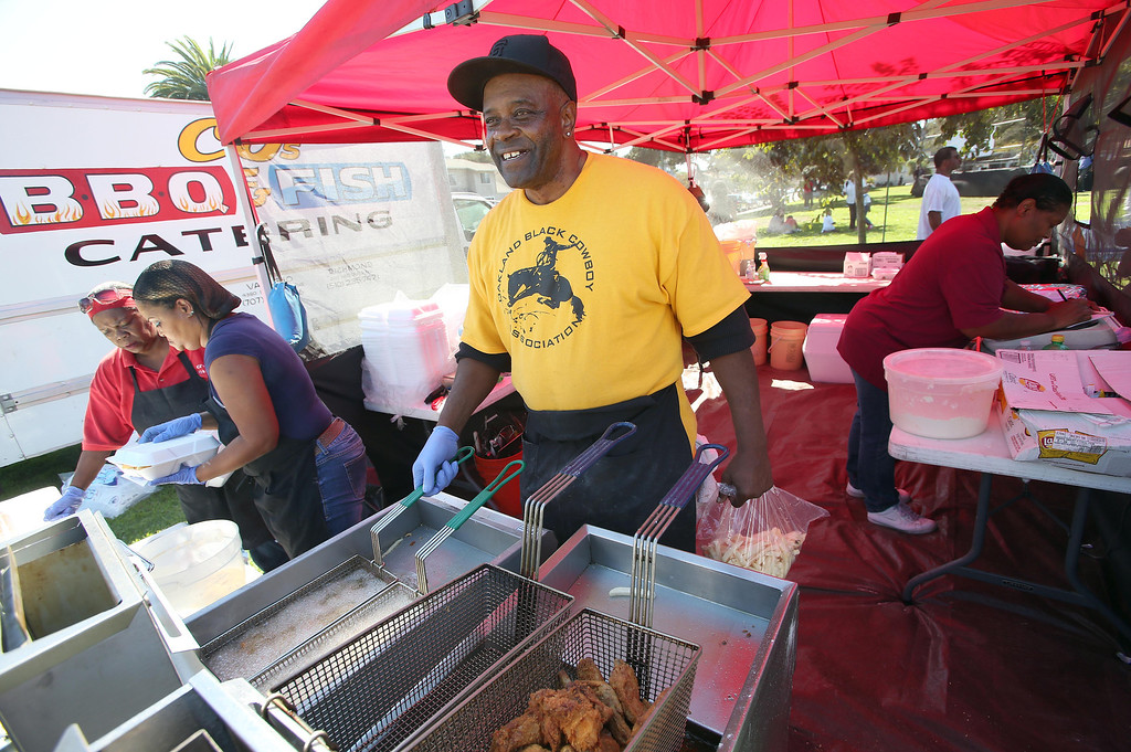 """. Charles \""""C.J.\"""" Evans, of Richmond, cooks catfish during the 39th annual Oakland Black Cowboy Parade and Heritage Festival at De Fremery Park in Oakland, Calif., on Saturday, Oct. 5, 2013. The event also featured food, entertainment and pony rides for kids. The Oakland Black Cowboy Association began in 1975 and educates the public about the role that black cowboys played in history and building of the west. (Jane Tyska//Bay Area News Group)"""