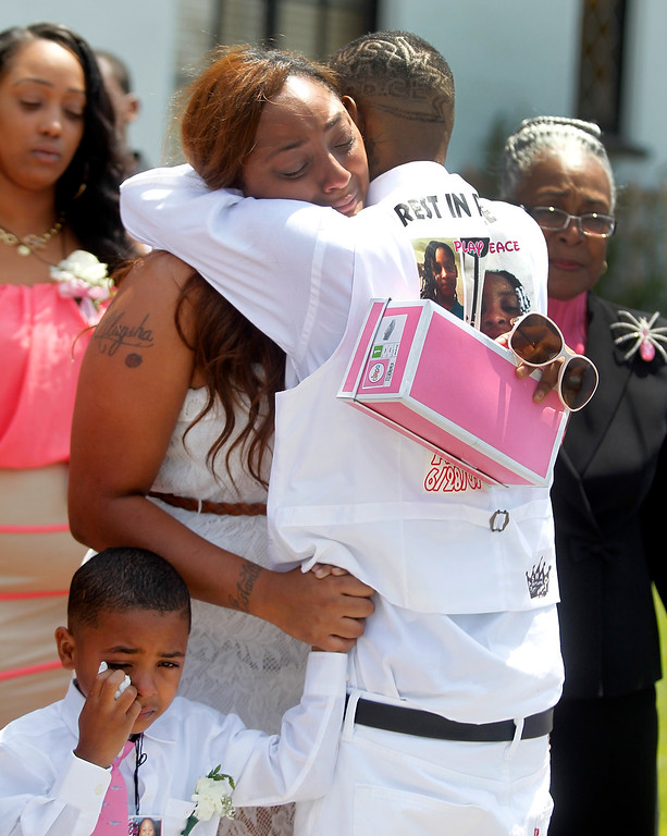 . Chiquita Carradine, center, gets a hug as she leaves McNary-Williams-Jackson Mortuary  after funeral services for her daughter Alaysha Carradine ,8, on Tuesday, July 30, 2013 in Oakland, Calif.  Alaysha Carradine was shot and killed during a sleepover at a friends house in the 3400 block of Wilson Avenue earlier this month in Oakland.   (Aric Crabb/Bay Area News Group)