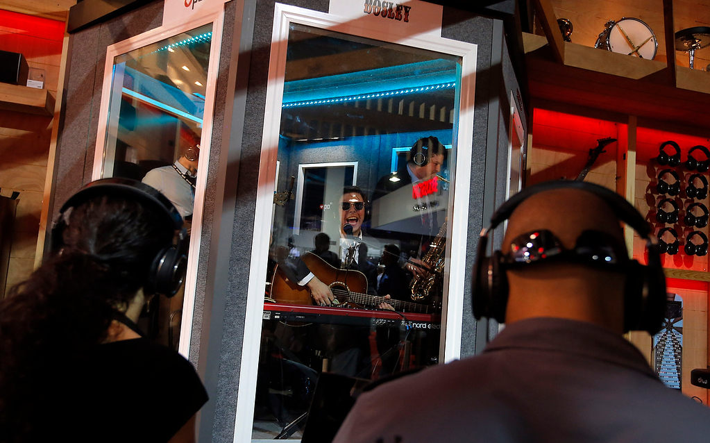 . Bosley, center, performs in a soundproof booth as show attendees listen with headphones at the Polk Audio booth at the International Consumer Electronics Show in Las Vegas, Wednesday, Jan. 9, 2013. (AP Photo/Jae C. Hong)