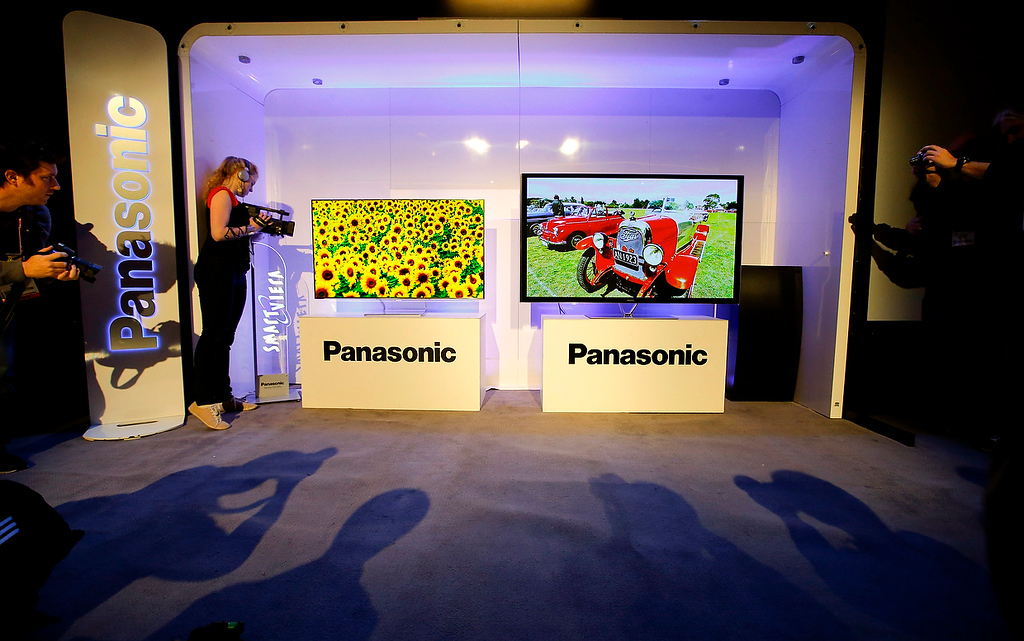. Show attendees photograph Panasonic\'s new televisions during a news conference at the International Consumer Electronics Show in Las Vegas, Monday, Jan. 7, 2013. (AP Photo/Jae C. Hong)