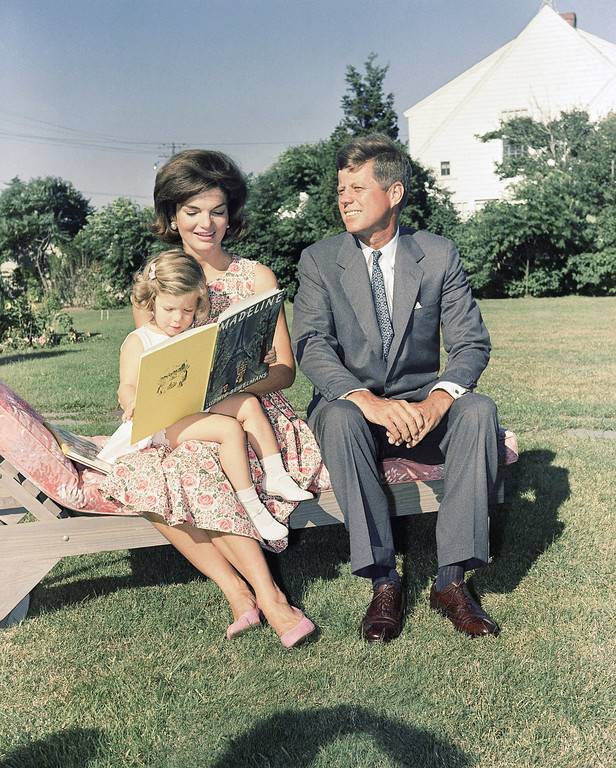 . In this July 25, 1960 file photo , Sen. John F. Kennedy, D-Mass., sits with wife, Jacqueline, as she reads to their daughter, Caroline, at Hyannis Port, Mass. (AP Photo)