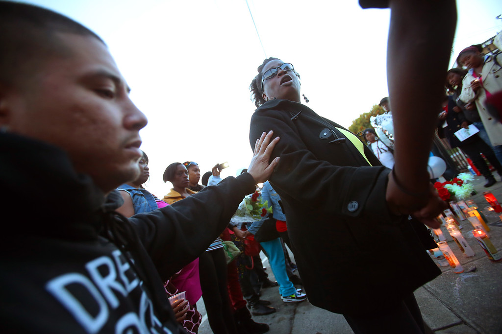 . Arthur Renowitkzky, left, puts his hand on the shoulder of Dinyal New, center, during a vigil for her son Lee Weathersby III onThursday, Jan. 2, 2014 in Oakland, Calif.  Weathersby,13, was shot and killed while coming home from the Boys and Girls Club on New Year\'s Eve.  (Aric Crabb/Bay Area News Group)