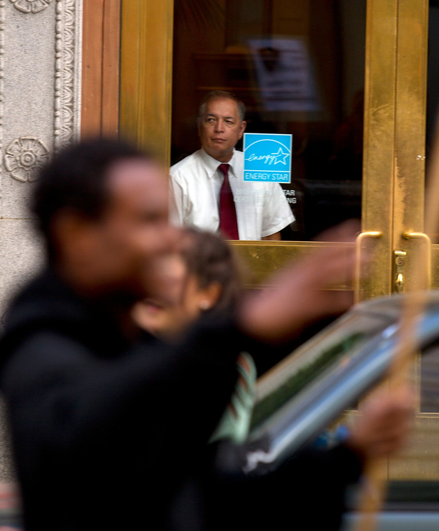 . A security guard watches passing demonstrators on Broadway during a protest of the verdict in the Trayvon Martin murder trial last Saturday in Sanford, Fla., Monday, July 15, 2013 in Oakland, Calif. (D. Ross Cameron/Bay Area News Group)