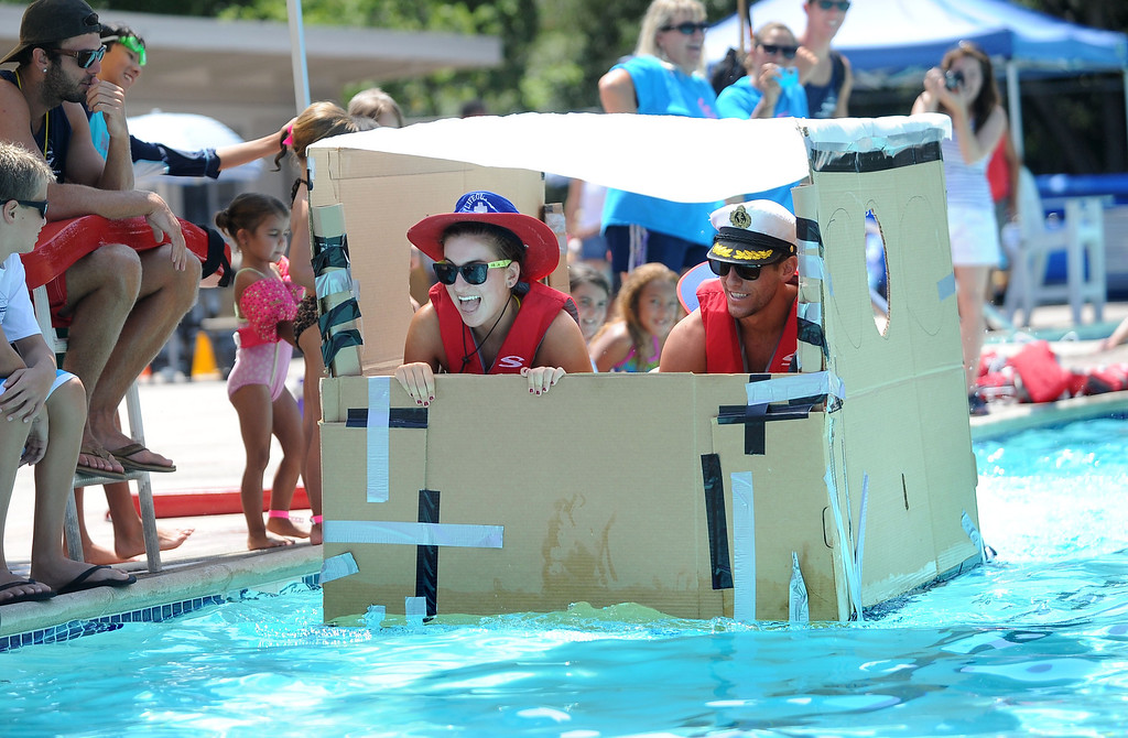 . Lifeguards Courtney Holcomb, and Tim Jones, are paddled across a pool by a fellow lifeguard in their watercraft made of only cardboard, recyclables and duct tape during the Derby Day boat race held at Pleasant Hill Aquatic Park in Pleasant Hill, Calif., on Friday, July 19, 2013. (Doug Duran/Bay Area News Group)