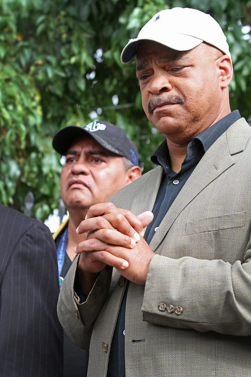 . Preston Turner,from the neighborhood crime prevention council, right, and community activist Jose Ortiz, left listen intently to fellow community members speak at a press conference at the site where Judy Salamon was shot and killed driving on Fern Street in Oakland, Calif., on Friday, July 26, 2013. Council members Noel Gallo and Libby Schaaf along with residents of the Maxwell Park neighborhood called a press conference to tell their stories of robberies, burglaries, and violent crime  in their neighborhood  and throughout Oakland. (Laura A. Oda/Bay Area News Group)