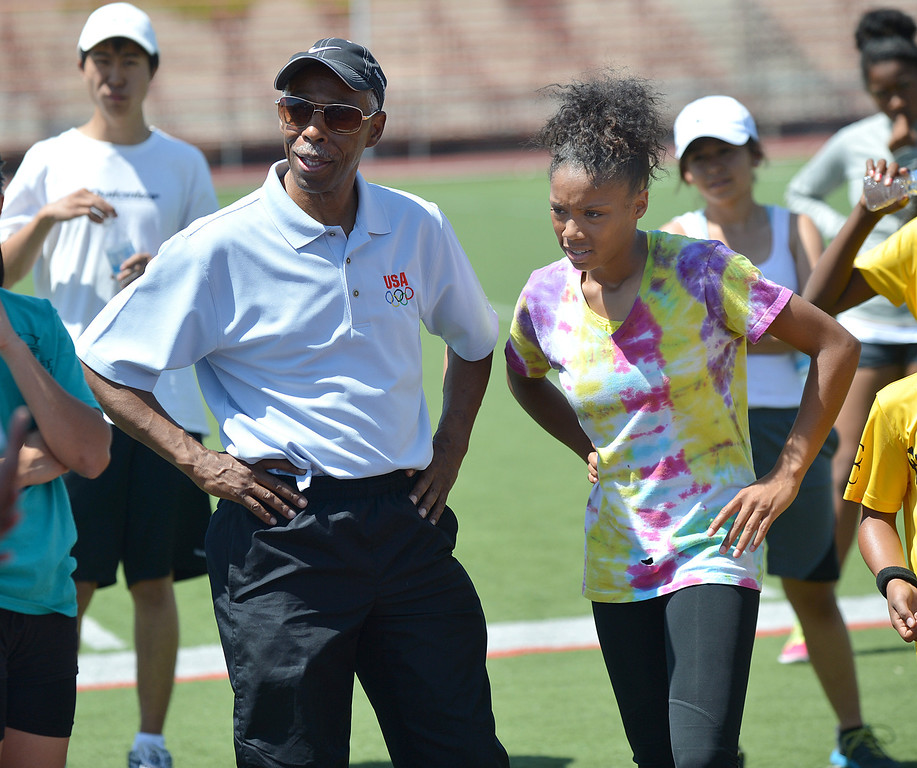 . Eddie Hart, left, of Pittsburg, the founder of the All-In-One non-profit, watches a track demonstration with Kaliyah Huddleston, 15, of Pittsburg, during the Eddie Hart All-In-One Foundation track and field clinic at Pittsburg High School in Pittsburg, Calif., on Saturday, May 4, 2013. (Dan Rosenstrauch/Staff Archives)