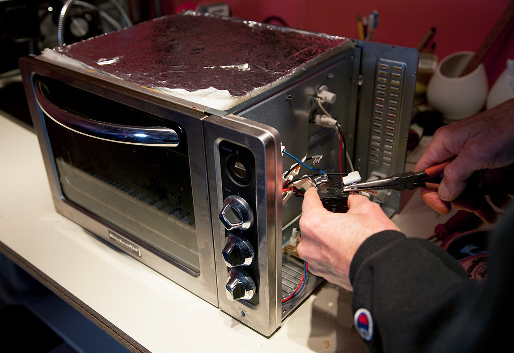 . John Eaton reattaches the contacts of the function dial of a neighbor\'s toaster oven after repairing it at his home in Palo Alto, Calif. on Friday, Feb. 15, 2013.   (LiPo Ching/Staff)
