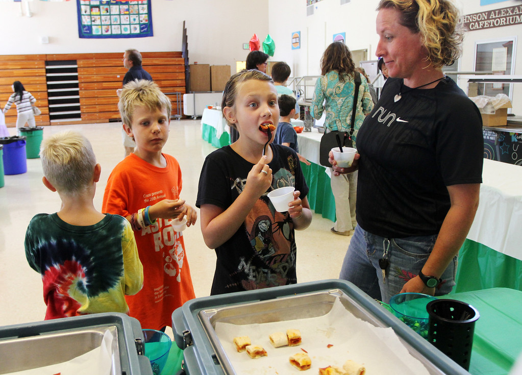. Loren Olsen, 10, center, samples a pizza calzone with her mother Brandy, right, and brothers Ian, 6, and Lance, 8, during a �tasting day� at Jane Lathrop Stanford Middle School in Palo Alto on Friday, Aug. 9, 2013. All three children will attend Ohlone Elementary School this year. The Palo Alto Unified School District used the free event to showcase 23 new menu items, several of which were touted as local and organic. (Kirstina Sangsahachart/ Daily News)
