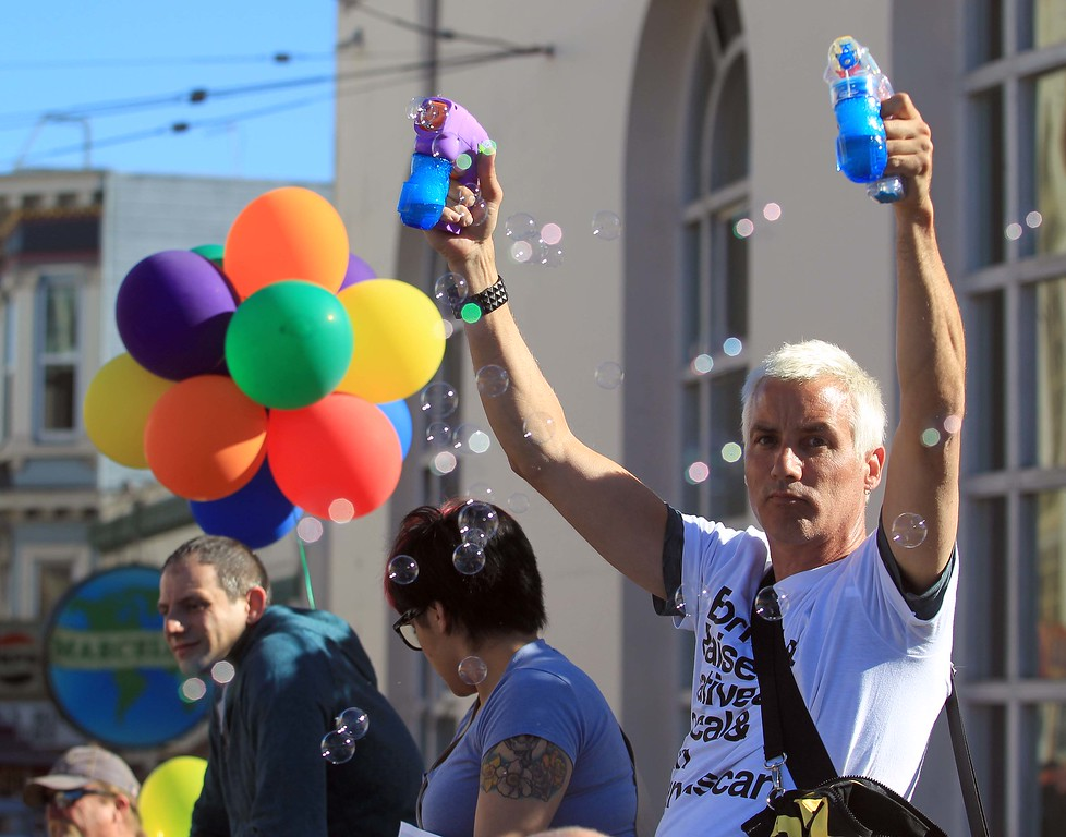 . Toby Fifield, of San Francisco, right, blows bubbles during a gathering on Castro Street in San Francisco, Calif., on Wednesday, June 26, 2013. The U.S. Supreme Court dismissed California\'s Proposition 8 and declared the 1996 Defense of Marriage Act unconstitutional. (Jane Tyska/Bay Area News Group)