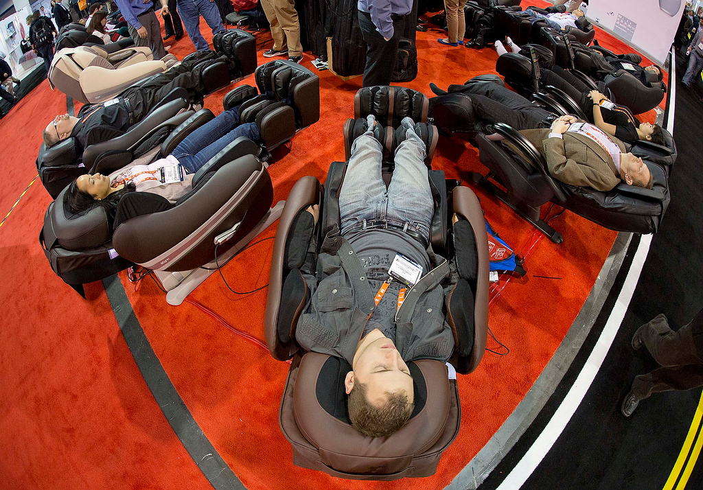 . Industry affiliates try out a display of massage chairs at the Consumer Electronics Show, Wednesday, Jan. 9, 2013, in Las Vegas. (AP Photo/Julie Jacobson)