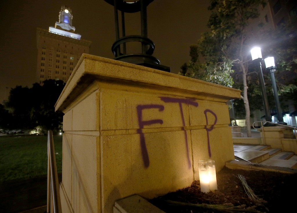 . Two candles burn next to graffiti at Frank Ogawa Plaza in downtown Oakland, Calif., early Sunday, July 14, 2013. Protesters also lit several small fires on Telegraph Avenue and smashed windows after learning that George Zimmerman had been found not guilty in the shooting death of Trayvon Martin in Sanford, Fla. (Jane Tyska/Bay Area News Group)