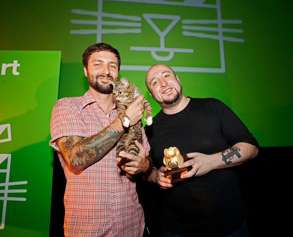 . In this Aug. 30, 2012 publicity photo provided by the Walker Art Center, festival attendee, Mike Bridavsky and his cat Lil Bub, left, pose with Golden Kitty Award-winner William Braden, at the Walker Art Center Internet Cat Video Festival in Minneapolis. (AP Photo/Walker Art Center, Gene Pittman)