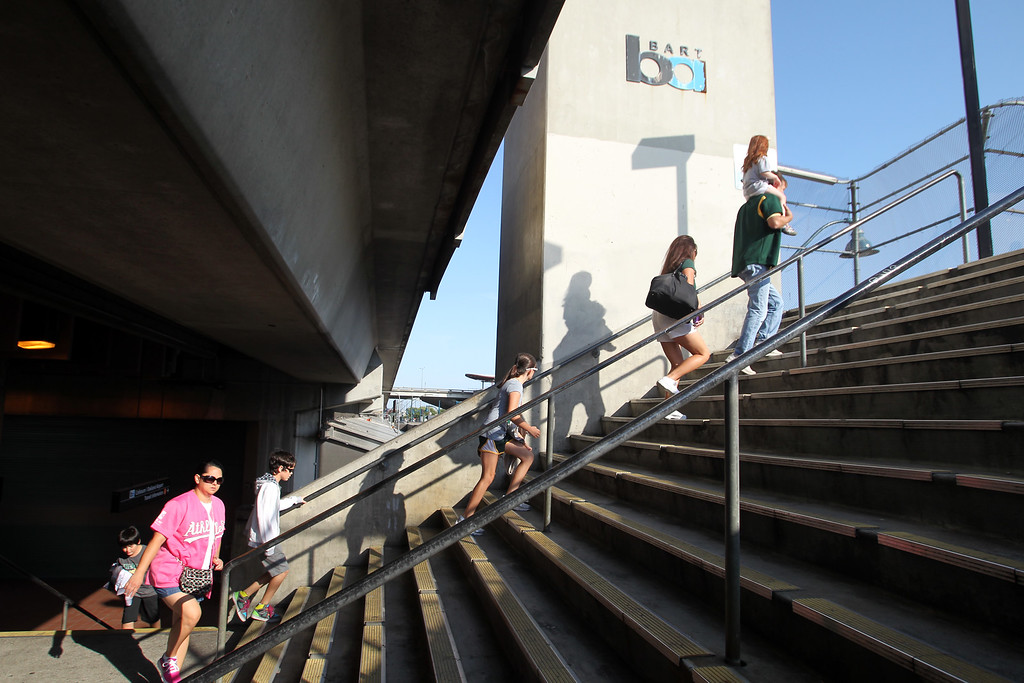 . Fans take the stairs to the BART-Coliseum corridor as the Oakland Athletics host the Chicago Cubs on their first appearance at O.co Coliseum in Oakland, Calif., on Tuesday, July 2, 2013. The BART remains closed on their second day of strike. (Ray Chavez/Bay Area News Group)