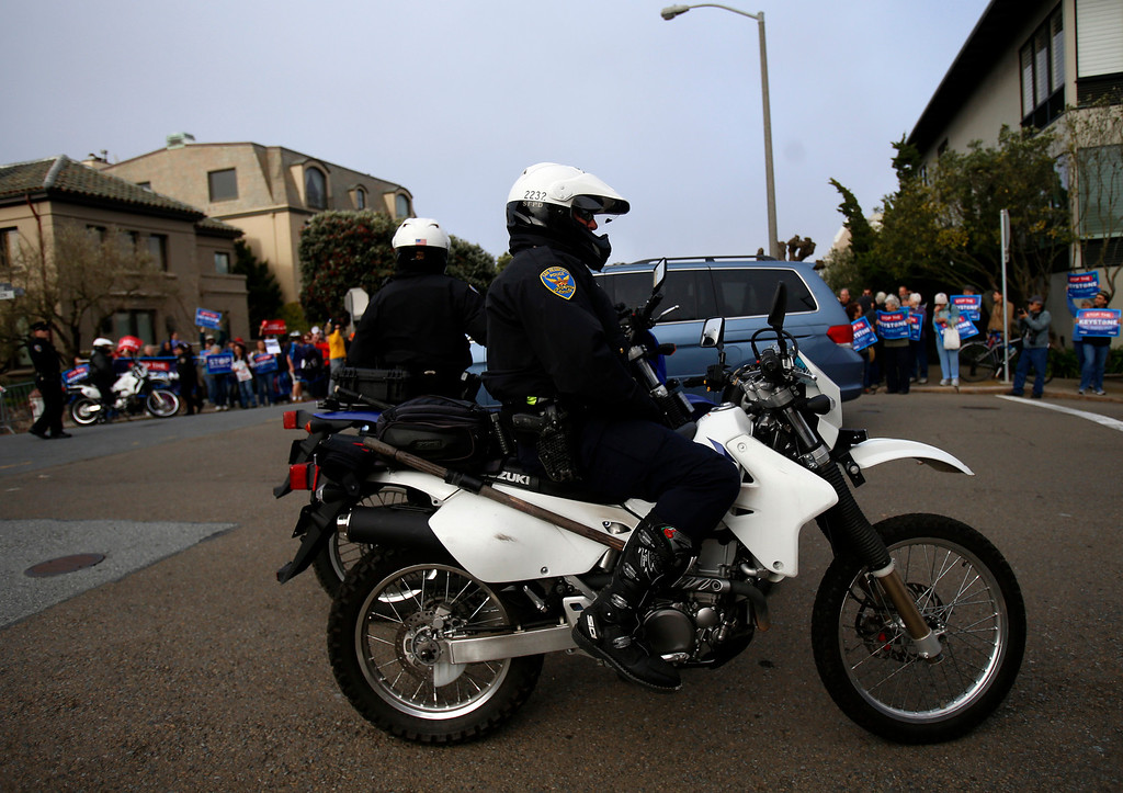 . San Francisco police officers at the corner of Pacific Avenue and Lyon Street watch over protesters against the plan to build a pipeline from Canada to Texas, called the Keystone XL pipeline, in Pacific Heights in San Francisco, Calif., on Wednesday, April 3, 2013.  (Nhat V. Meyer/Staff)