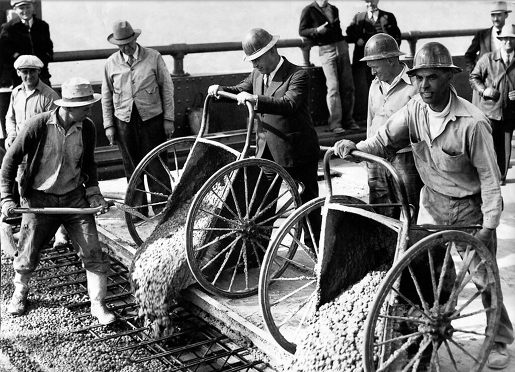 . October 15, 1936 - Bridge Superintendent Charles Andrews (center, in suit) holds the last wheelbarrow of cement as George Termer shovels. With them are, left to right, William Christiansen, C. T. Smith, superintendent of Biggs and Rogers Co., John Larson and S. A. Cordoza. (Oakland Tribune Photo)